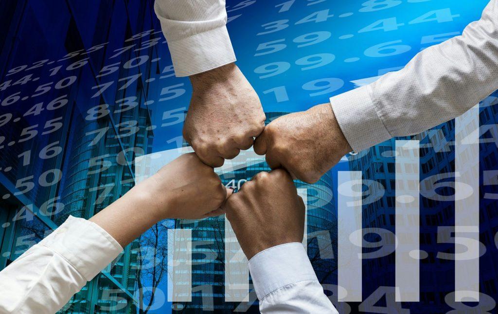 Ekspansja międzynarodowa szansą dla polskich producentów - 4 dłonie ułożone w pięść stykają sie na znak współpracy.