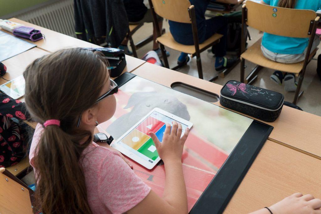 Szkoły i placówki wracają do stacjonarnej pracy - dzieci siedzą w ławkach szkolnych w klasie.