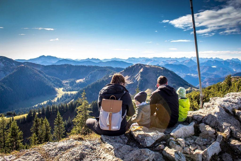 5 sposobów na aktywną majówkę - ludzie z dziećmi siedzą na szczycie góry