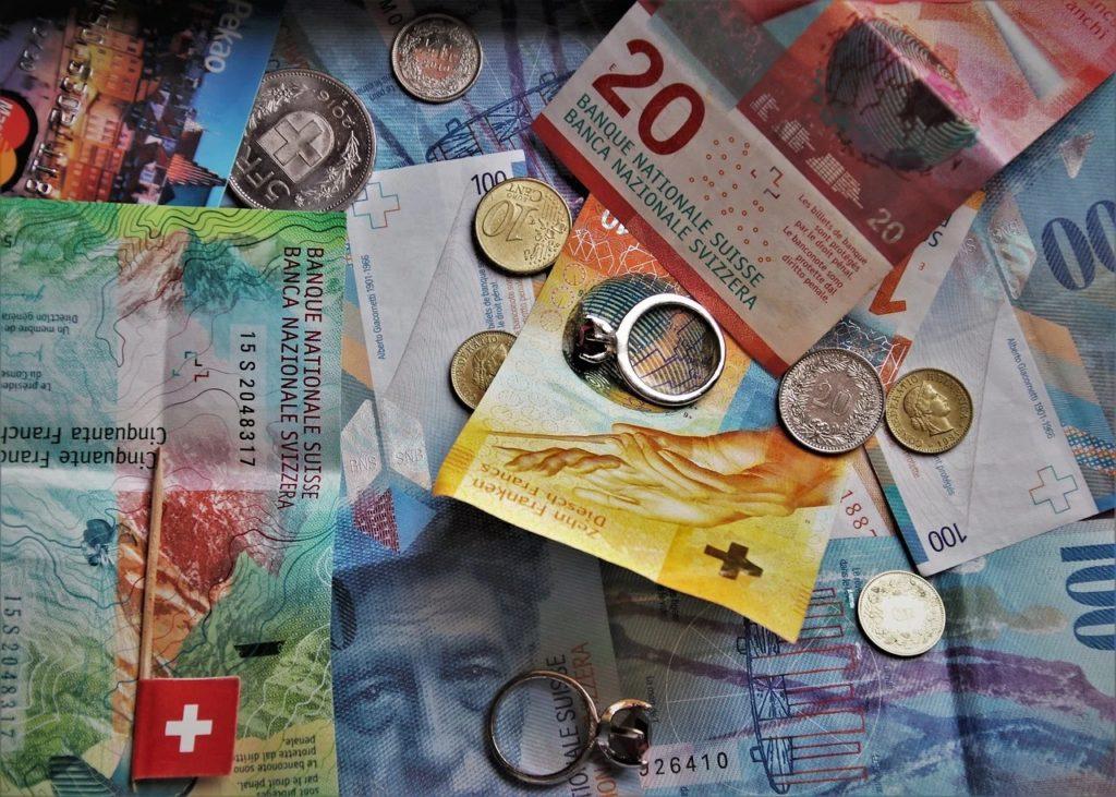 Jest wyrok TSUE. Frankowicze masowo ruszą do sądów? - monety i banknoty w rozsypce na stole.