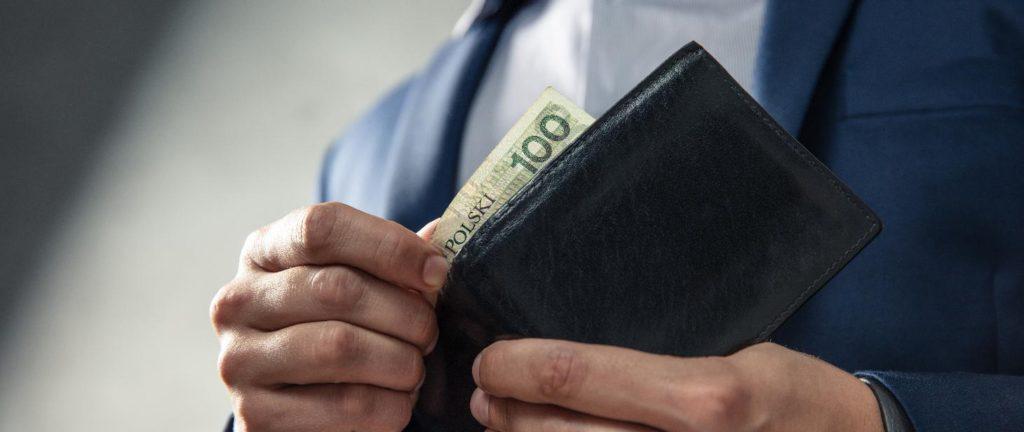 Płaca minimalna i stawki godzinowe w 2022 r. - meżczyzna wyciąga banknot  z portfela.