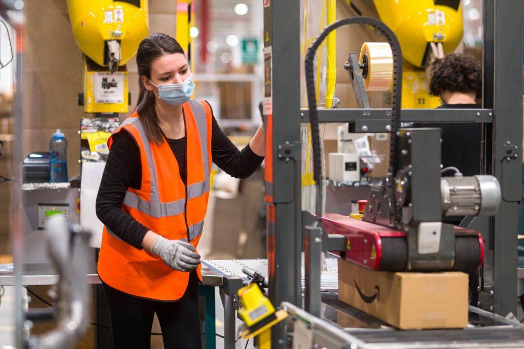 Amazon podnosi pensje dla pracowników - kobieta w kamizelce odblaskowej i z maseczką na twarzy stoi przy maszynie.