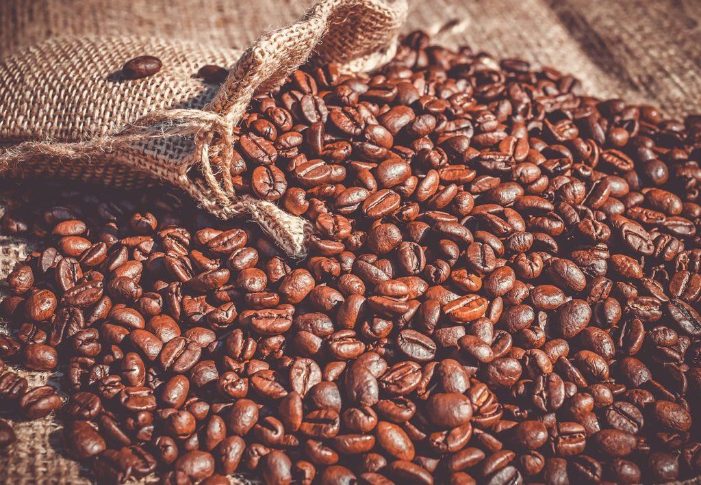 Rynek kawy w Polsce i na świecie - kawa wysypana z worka na stół.