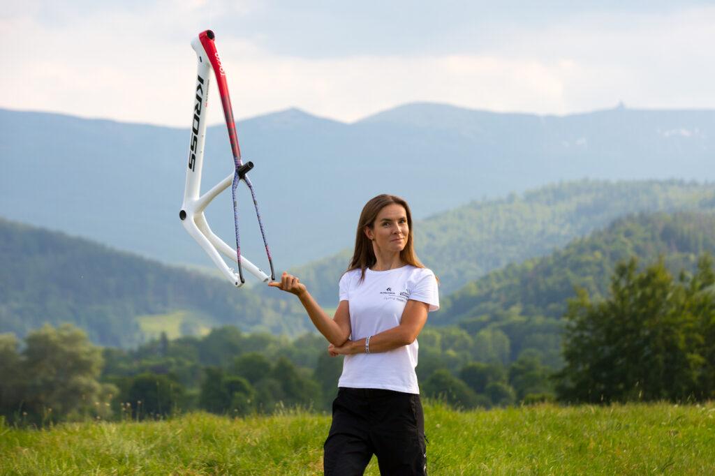 Boom na rowery. Rośnie popyt na modele elektryczne - kobieta stoi na trawie i trzyma w reku rame od roweru.