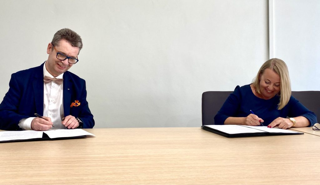 PARP i SGH razem dla przedsiębiorczości - kobieta i mężczyzna siedzą przy stole i podpisują dokumenty.