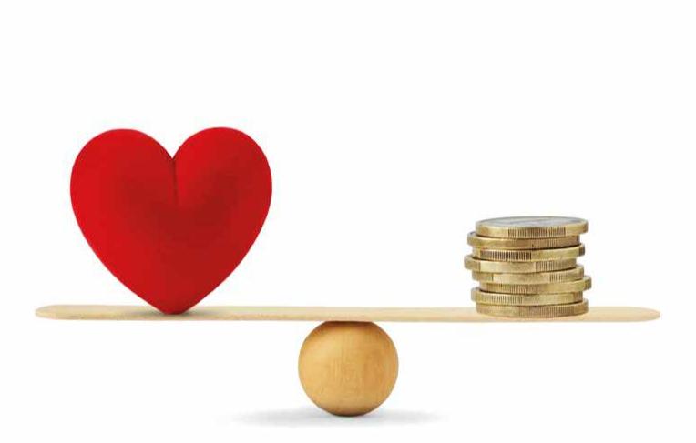 Kierunek na financial wellness. Jakich benefitów poszukują dziś pracownicy? - czerwone serce i pieniądze w postaci monet na szali.