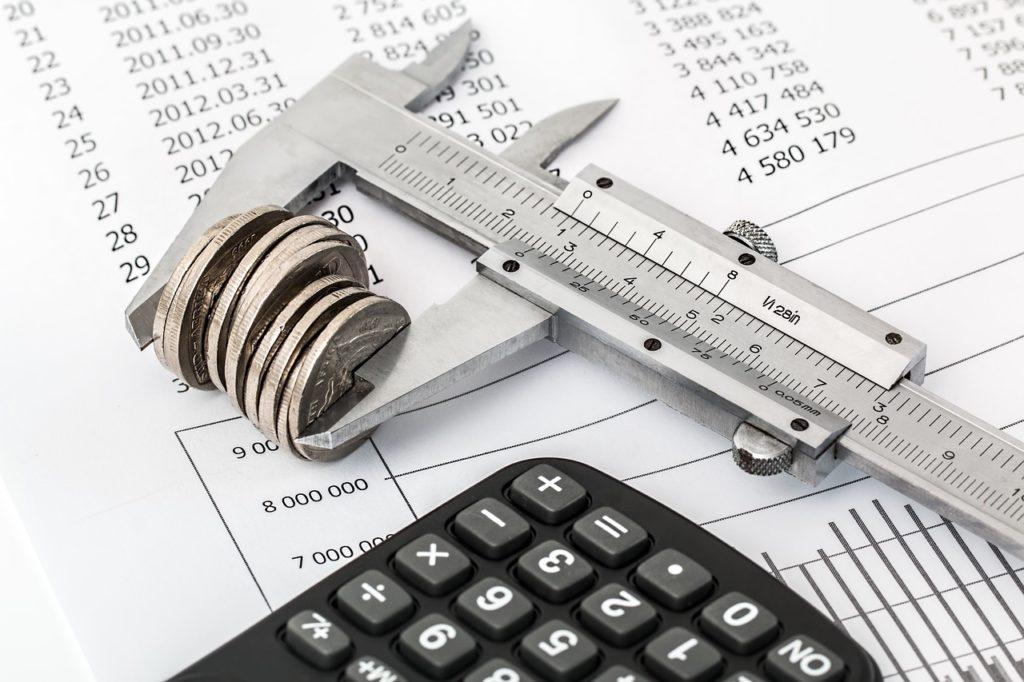Polacy nie opłacają polisy AC - umowa, kalkulator i pieniądze leżą na stole.