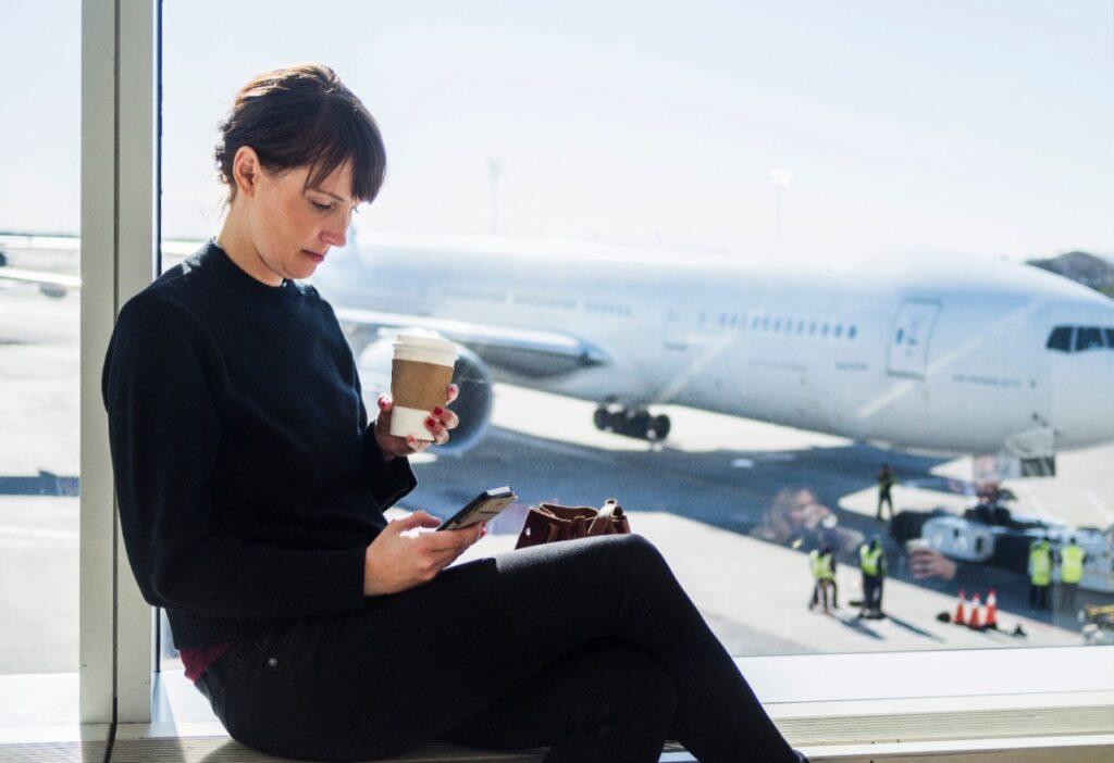 Loty krajowe powoli wracają na właściwy kurs - kobieta siedzi na lotnisku, w tle zaparkowany samolot.