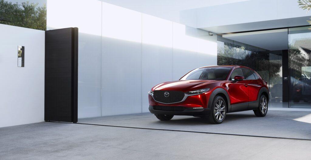 """Mazda MX-30 – pierwszy """"elektryk"""" w cenie benzynowego odpowiednika - czerwone auto zaparkowane  przed budynkiem."""