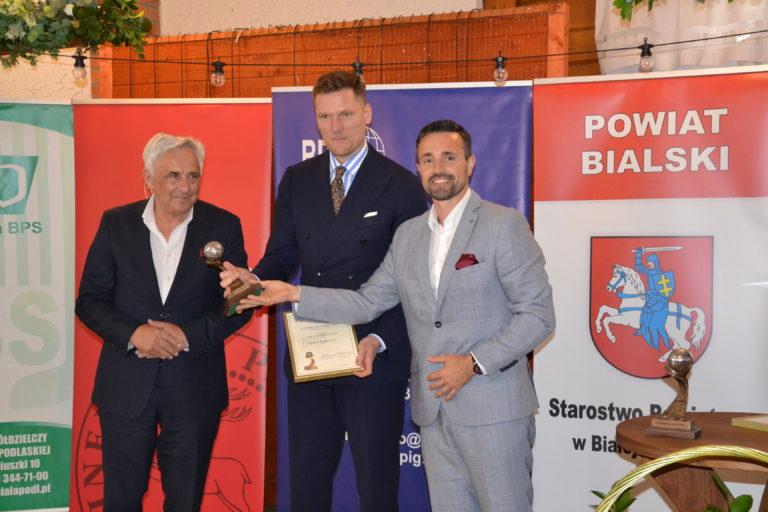 Krynica Vitamin z nagrodą Lider Przedsiębiorczości- trzej mężczyźni stoją na scenie i trzymają  statuetkę w rękach.