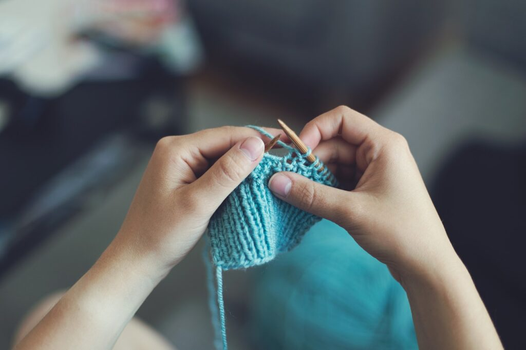 Jak zamienić pasję w dochodowy biznes, czyli jak sprzedawać rękodzieło?   - kobieta robi wełniane ubranie na drutach.