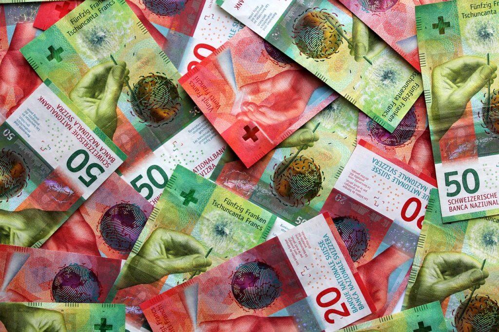 Drugie dno drogiego franka szwajcarskiego - banknoty franka szwajcarskiego rozsypane na stole.