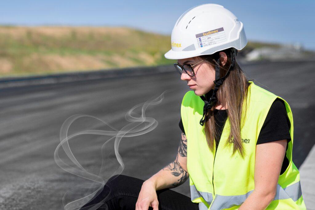Budimex i Lotos Asfalt pracują nad pachnącym asfaltem - kobieta siedzi na drodze asfaltowej.
