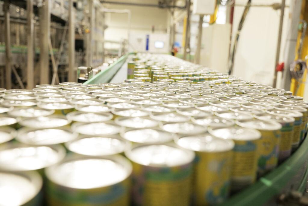 Napoje Ekipa wchodzą na rynek. Produkcja w Krynicy Vitamin idzie pełną parą - hala produkcyjna z puszkami na taśmie.
