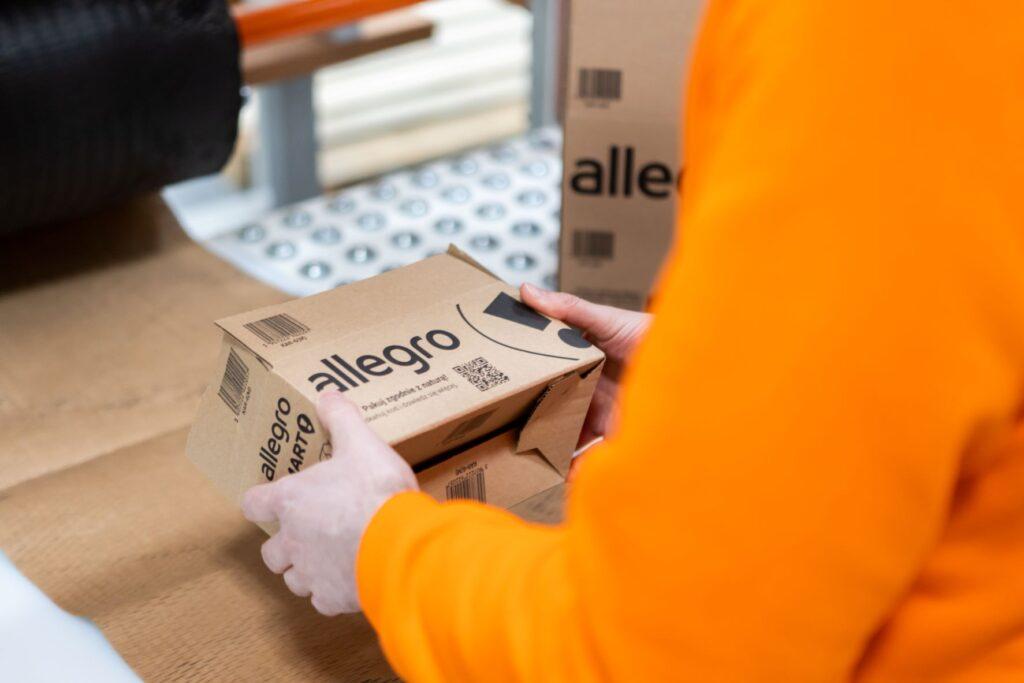 Allegro startuje z nową usługą dla sprzedawców - mężczyzna w pomarańczowej bluzie trzyma kartonowa paczkę w rekach.
