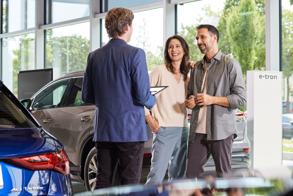 Z łatwością stworzysz Audi swoich marzeń - dwóch mężczyzn i kobieta stoją w salonie samochodowym obok aut i rozmawiają.