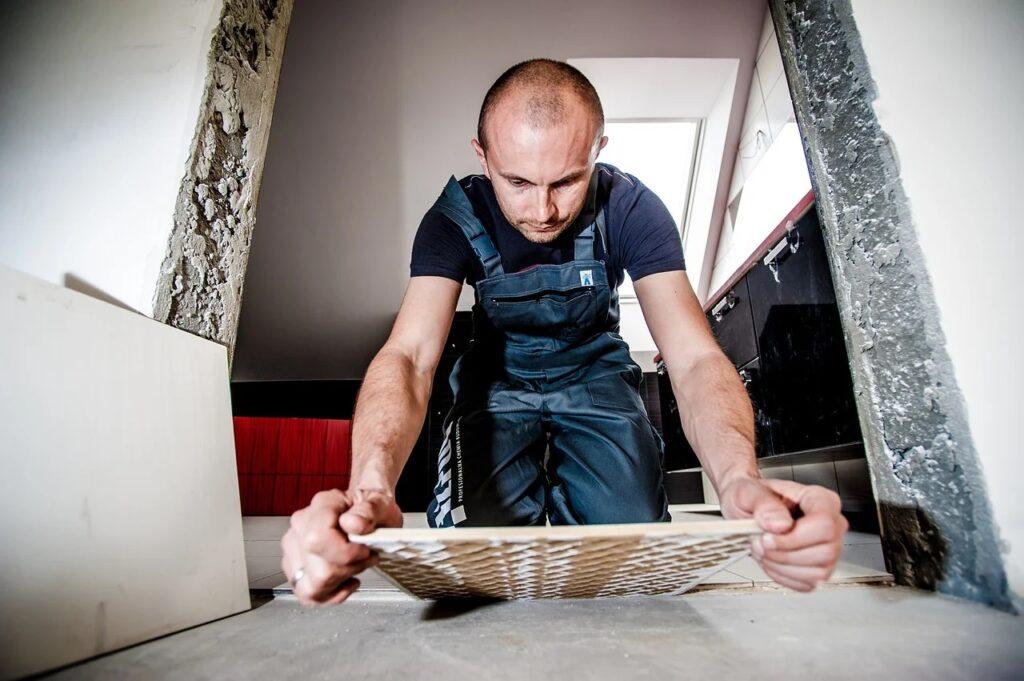 Rynek pracy oczekuje pracowników z Białorusi. Stawką nawet 0,5 mln osób - mężczyzna układa płytki na podłodze.
