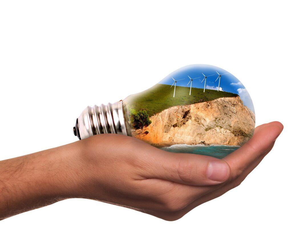 Transformacja klimatyczna oznacza dla banków ogromne możliwości biznesowe - na dłoni mężczyzny leży żarówka.