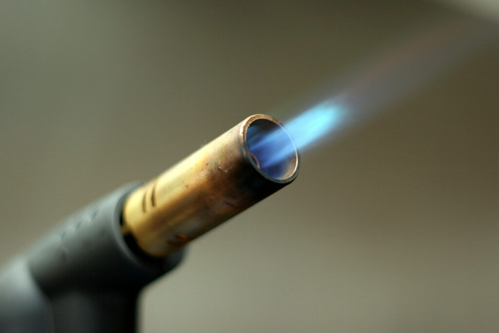 Ceny gazu znowu szybują w górę - kawałki rury gazowej, z której wydobywa się gaz.