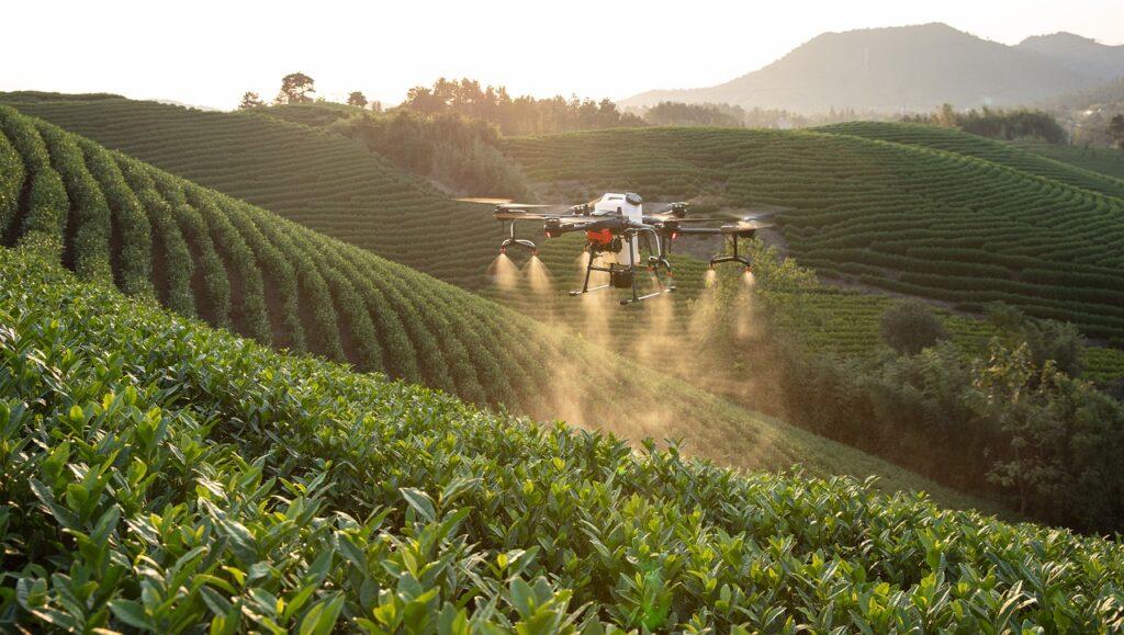 Drony zrewolucjonizują rolnictwo - dron robi opryski nad polem uprawnym.