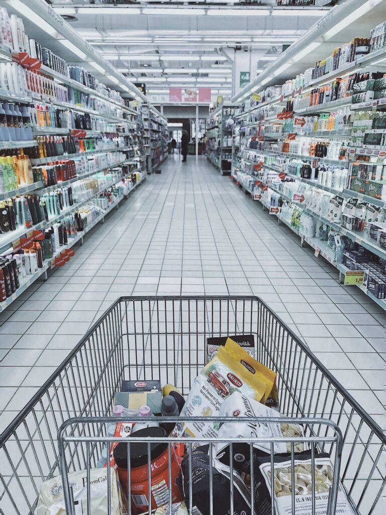 """Alkohol coraz częściej """"znika"""" z półek - koszyk z zakupami w supermarkecie."""