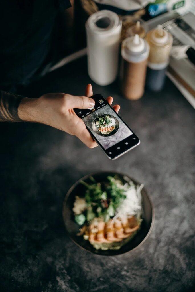 Influencerzy pod lupą UOKiK - mężczyzna robi zdjęcie jedzenia.