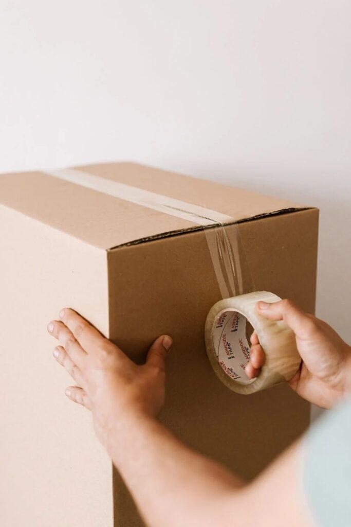 Kolejna innowacja dla klientów InPost -mężczyzna zakleja kartonowe pudełko taśmą.
